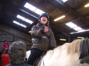 Chloe smiling on a horse